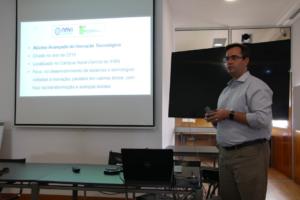 Descrição da imagem: Professor Fabiano Papaiz em primeiro plano apresentando slides em uma tela de projeção.
