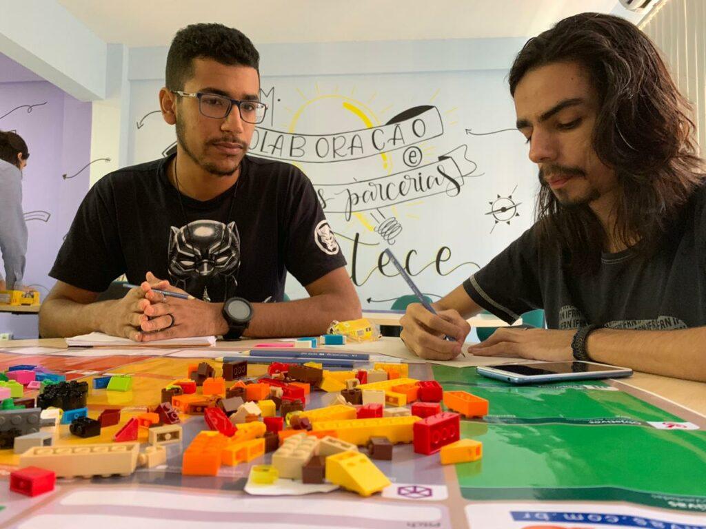 Descrição da imagem: Dois bolsistas trabalhando no projeto da oficina. Eles estão sentados, um deles está escrevendo em um papel. Sobre a mesa, material para a construção do projeto: peças de lego coloridas, cartolina e papel.