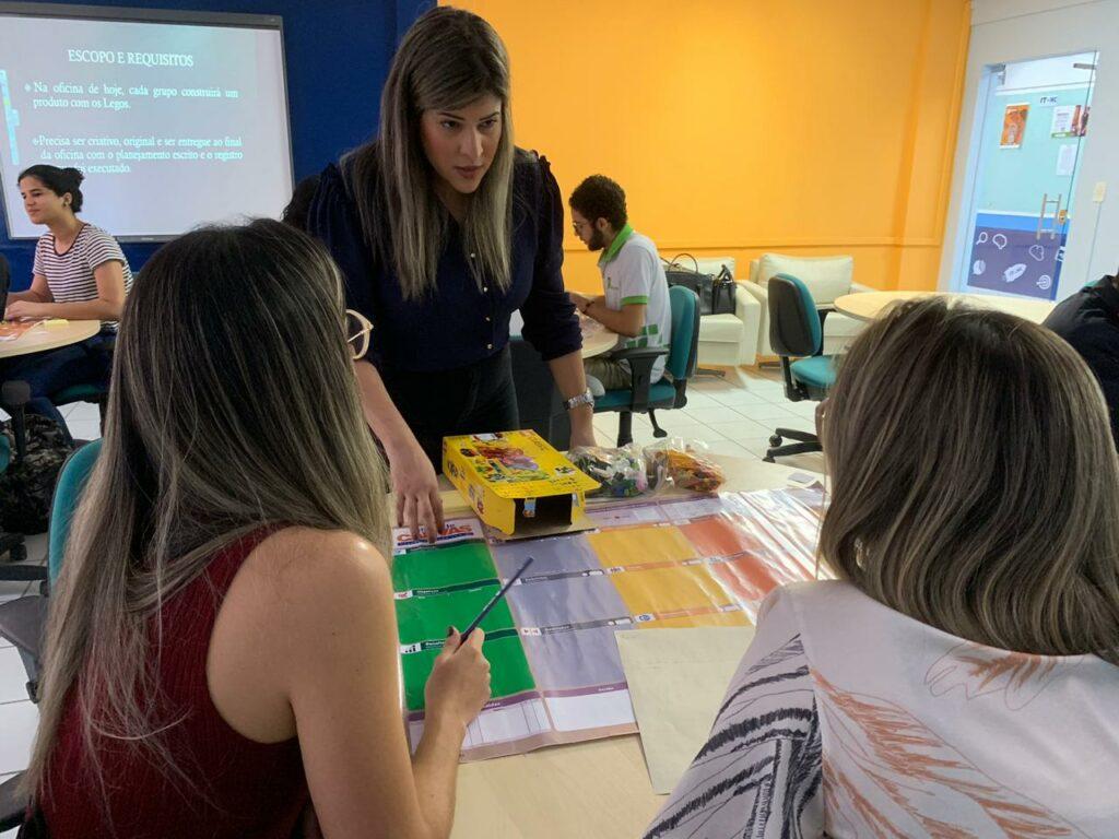 Descrição da imagem: A ministrante da oficina, Milena Duarte dá explicações para uma dupla de participantes.